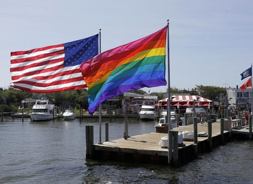 American flag and Gay Pride flag fly side by side on Fire Island