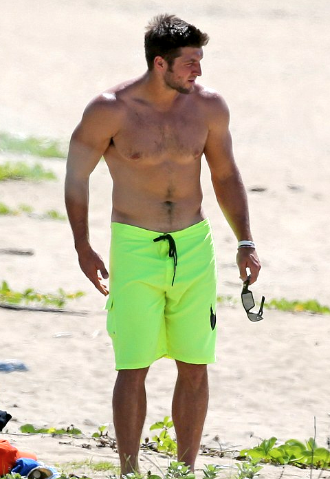 Hunky and shirtless Tim Tebow hanging at the beach in Hawaii
