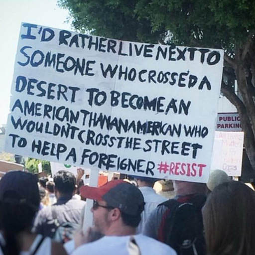 """A pro-immigration supporter with a sign which reads, """"I'd rather live next to someone who crossed a desert to become an American than an American who wouldn't cross the street to help a foreigner #resist"""""""