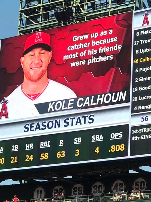 """Scoreboard during baseball game highlights a player reading, """"Grew up as a catcher because most of his friends were pitchers."""""""