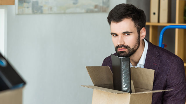 Stock photo showing a fired male employee sitting at his desk