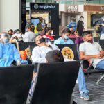 People at an airport wearing face masks