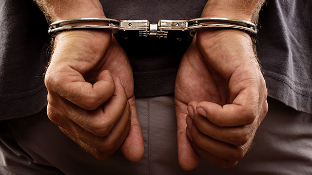 Photo of a man's hands cuffed behind his back