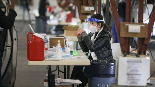 A FEMA healthcare worker prepares a COVID-19 vaccination