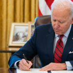 President Joe Biden signs documents in the Oval Office