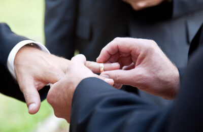 A gay man places a wedding ring on the finger of his husband