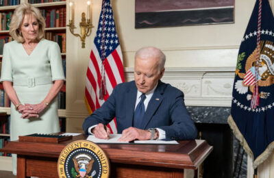 First Lady Jill Biden watches as President Joe Biden signs legislation into law