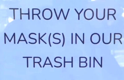 """A sign at Fiddleheads Cafe reads, """"Throw your masks in our trash bin"""""""